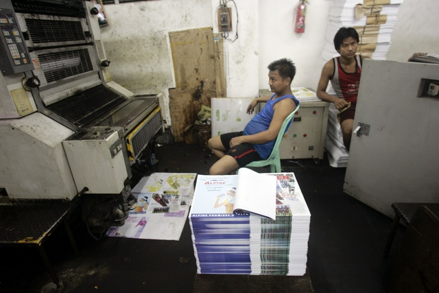 Newspapers undergo production at a printing house in Rangoon on 17 November 2011. (Reuters)