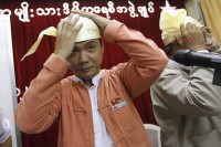 Elected candidate Zayar Thaw (L) and his counterparts from the National League for Democracy (NLD) Party try on Burma's traditional cap, to be worn in the Parliament, at the NLD head office in Rangoon on 21 April 2012. (Reuters)