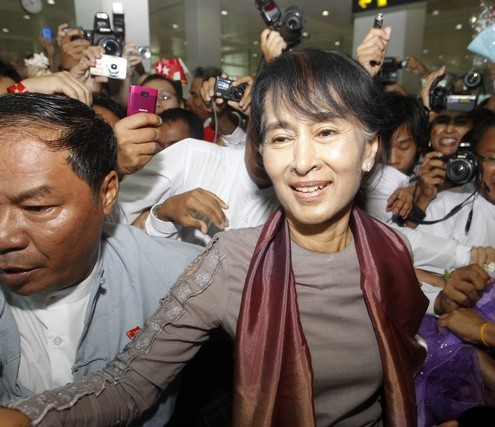 Myanmar's pro-democracy leader Aung San Suu Kyi walks among her supporters as she arrives at Yangon international airport