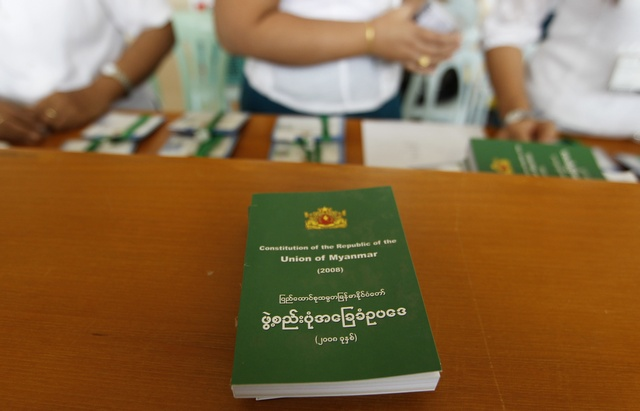 Staff sell copies of Burma's constitution at the Lower House of Parliament in Naypyidaw on 9 July 2012. (Reuters)