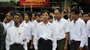 People stand in attention during an event marking the anniversary of Martyrs' Day at NLD head office in Yangon
