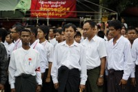 People stand in attention during an event marking the anniversary of Martyrs' Day at the National League for Democracy (NLD) head office in Rangoon on 19 July 2012. (Reuters)