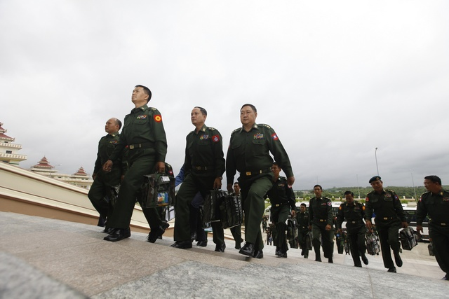 Military members of Parliament arrive to attend a meeting at the Lower House of Parliament in Naypyitaw on 9 July 2012. (Reuters)