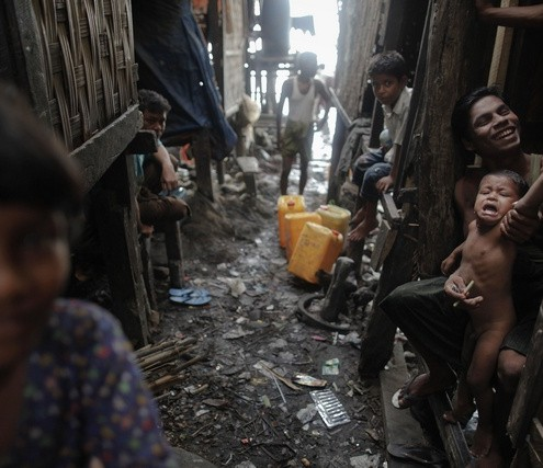 Myanmar Rohingya people pass time in their slum near the sea in the town of Sittwe
