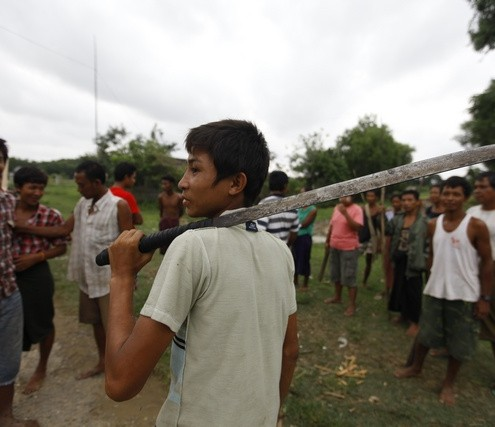 A Buddhist man holds a machete as he and other members of the community guard their homes in Sittwe