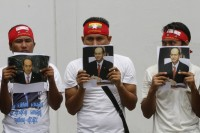 Burmese citizens living in Thailand held portraits of Burma's President Thein Sein as they gather outside the Burmese embassy in Bangkok on 24 July 2012. (Reuters)