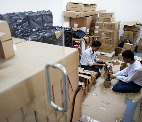 Technicians unpack new credit card readers at Myanmar's central bank branch in Yangon