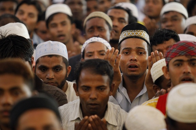 "An ethnic Rohingya from Burma and living in Malaysia, wearing a traditional Malay ""songkok"" prayer cap, recites prayers at a mosque in Kuala Lumpur on 17 June 2012 as sectarian riots engulf Burma's Arakan state. (Reuters)"
