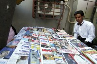 A street vendor sells local newspapers, magazines and books in Rangoon on 21 November 2011. (Reuters)