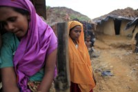 Rohingya women stand in front of their makeshift home in an unregistered Rohingya refugee camp in Teknaf on 17 June 2012. (Reuters)
