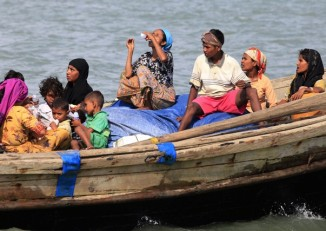 Rohingya people on a boat cross the river Naf, from Burma into Bangladesh, in Teknaf 11 June 2012. (Reuters)