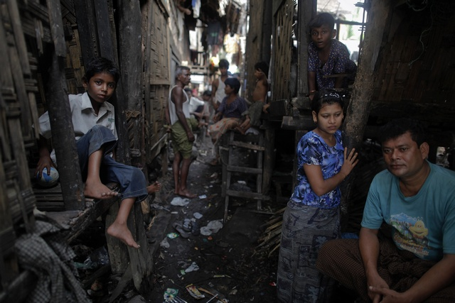 Rohingya people pass the time at their slum near the sea in the town of Sittwe on 19 May 2012. (Reuters)