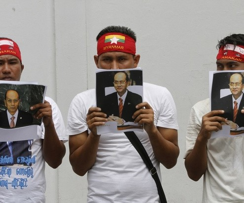 Buddhist Myanmar citizens living in Thailand held portraits of Myanmar's President Thein Sein as they gather outside the Myanmar embassy in Bangkok