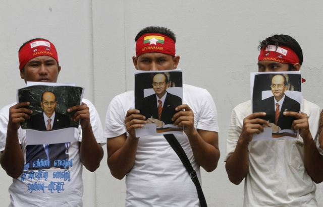 Burmese citizens living in Thailand held portraits of President Thein Sein as they gather outside the Burmese embassy in Bangkok on 24 July 2012. (Reuters)