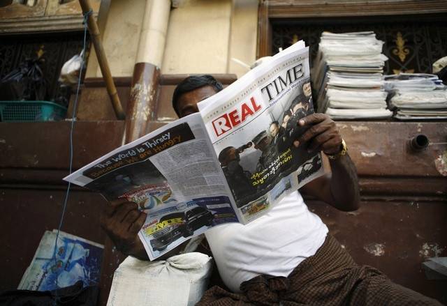 A man reads a weekly journal by the street in Rangoon on 29 March 2012. (Reuters)