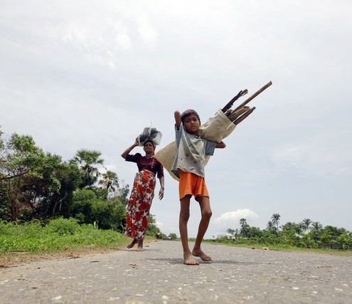 Rohingya people, displaced by recent violence, carry wood on a road outside Sittwe