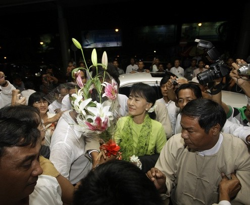 Myanmar pro-democracy leader Aung San Suu Kyi accepts flowers as she arrives at the airport to embark on a trip to the U.S. in Yangon