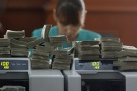 File photo of a worker counting Burmese kyat at a bank in Rangoon, April 2012. (PHOTO: Reuters)