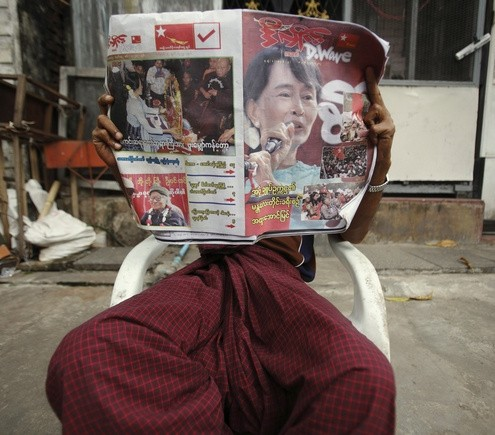 A man reads the newspaper outside his home near the ballot station during the by-elections in Yangon