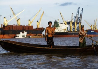 Fishermen maneuver their boat near the Thilawa port outside Rangoon. (PHOTO: Reuters)