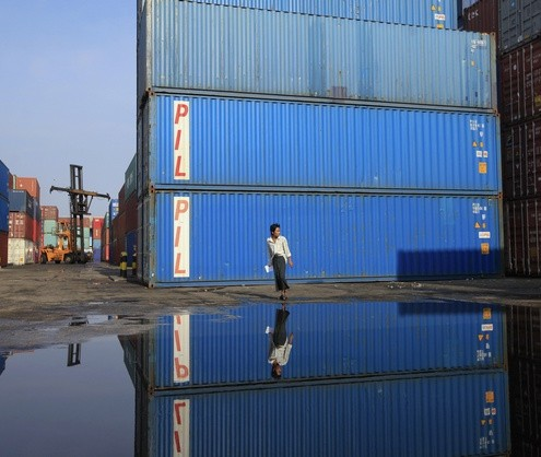 A worker walks in front of shipping containers at Yangon's port