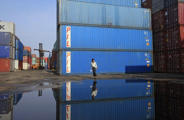 A worker walks in front of shipping containers at Port of Yangon. (PHOTO: Reuters)