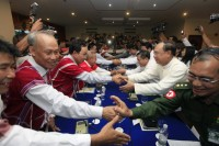 Delegates from the Karen National Union (KNU) (L) and the Burmese government's Union Peace Committee's members (R) shake hands after their meeting at Sedona hotel in Rangoon on 6 April 2012. (Reuters)