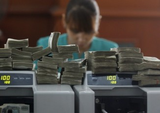 A worker counts Burma's kyat banknotes at the office of a local bank in Rangoon on 2 April 2012. (Reuters)