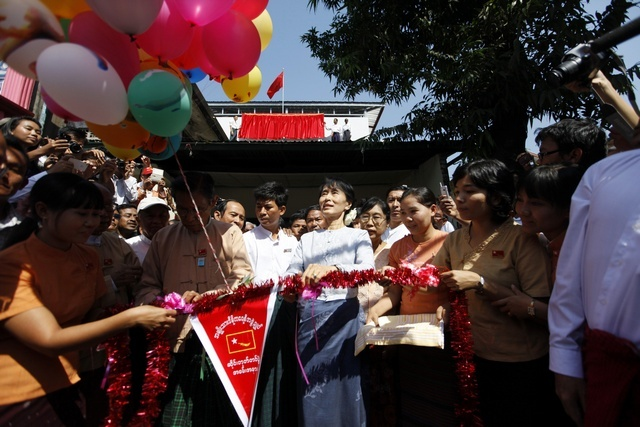 Aung San Suu Kyi (C) and NLD party leader Tin Oo (front row, 3rd L) cut a ribbon during a ceremony to inaugurate their party's new signboard at the NLD's head office in Rangoon on 9 January 2012. (Reuters)