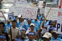 People hold posters during a march against civil war to mark the International Day of Peace in Rangoon on 21 September 21 2012. (Reuters)