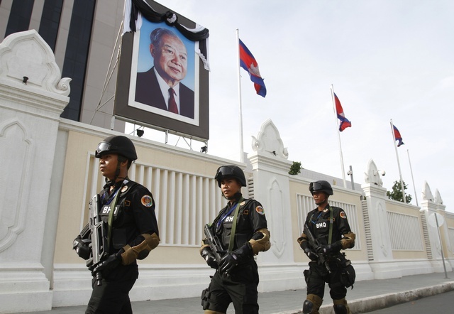 Cambodian government security forces walk in front of the Council of Ministers building as they patrol along a street ahead of the 21st ASEAN Summit and other related summits in Phnom Penh on 13 November 2012. (Reuters)