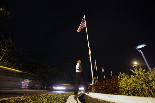 A man stands near a U.S. national flag as he sets up flags on a street in Rangoon on 18 November  2012. (Reuters)