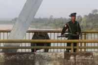 A Burma government soldier stands guard on a bridge over the Irrawaddy River near the city of Myitkyina, Kachin State.
