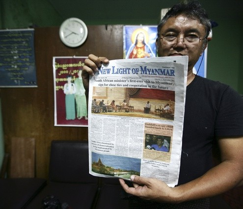 Editor-in-chief Than Myint Tun holds up a dummy of the New Light of Myanmar at its offices outside Naypyitaw