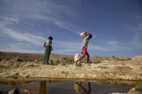 A boy carries a bag of sulphur sand to make copper near the controversial copper mine  in Sarlingyi township on 1 December 2012. (Reuters)