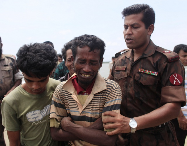A member the Bangladeshi border guard force comforts a Rohingya man after being arrested while trying to cross the border in Teknaf, 18 June 2012 (Reuters)