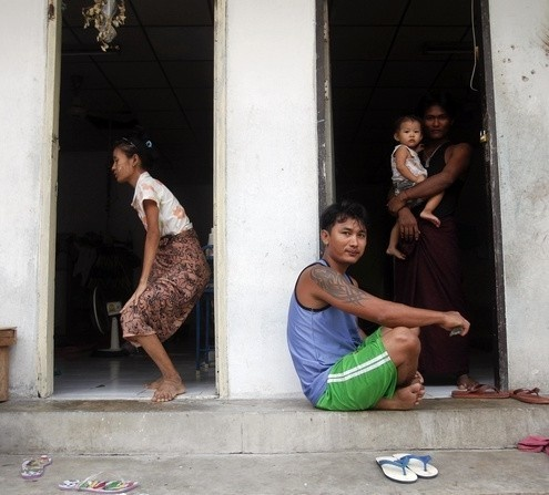 Burmese migrant workers pass the time outside a building where they live in the port town of Mahachai, near Bangkok on 24 September 2011. (Reuters)