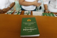 Staff sells copies of Burma's constitution at the Lower House of Parliament in Naypyidaw on 9 July 2012. (Reuters)