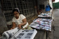 A woman arranges newspapers to sell by the street side in Rangoon on 31 December 2011. (Reuters)