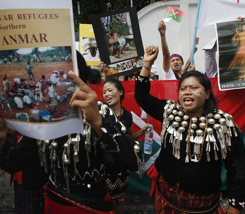 A group of native Kachin living in Thailand hold banners and shout slogans as they protest in front of Myanmar's embassy in Bangkok