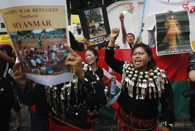 A group of native Kachin living in Thailand hold banners and shout slogans as they protest in front of Burma's embassy in Bangkok on 11 January 2013. (Reuters)