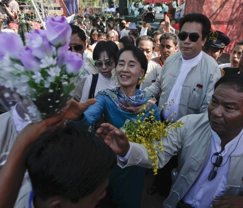 Myanmar's pro-democracy leader Suu Kyi accepts flowers from supporters as she attends a fund raising campaign for Education Network of her National League for Demorcracy party in Yangon