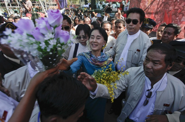 Myanmar's pro-democracy leader Suu Kyi accepts flowers from supporters as she attends a fund raising campaign for Education Network of her National League for Demorcracy party in Rangoon (NLD)