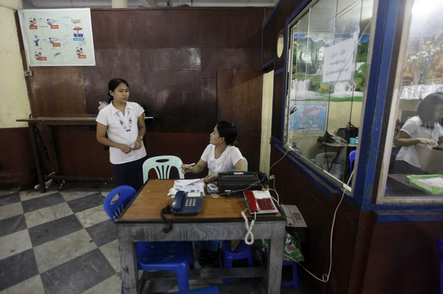 Workers chat as they sit in a public call office phone shop at the Post and Telecommunications division head office in Rangoon in 2012.  (PHOTO: Reuters)