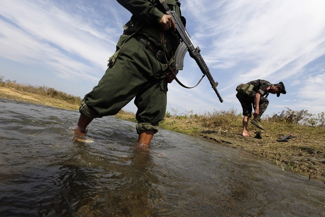 A soldier from the Kachin Independence Army (KIA) puts on his shoes as he and his comrade cross a stream towards the front line in Laiza, Kachin state, on 29 January 2013. (Reuters)