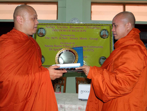 "Sansana Ramsi's Uttara (left) hands Wirathu (right) the monastery's ""freedom of religion"" award in Mandalay on 24 February 2013. (DVB)"