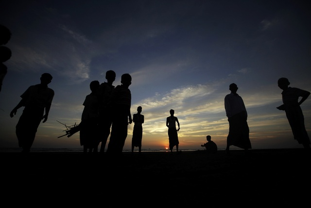 Muslims who escaped sectarian violence in Arakan state gather on beach near a refugee camp outside of the state capital Sittwe on 30 October 2012. (Reuters)