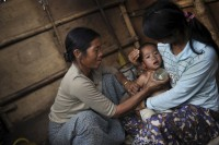 In this file photo, a Kachin woman applies traditional treatment to reduce her son's temperature at a refugee camp in Mansi Township, Kachin State, January 2013. (PHOTO: Reuters)