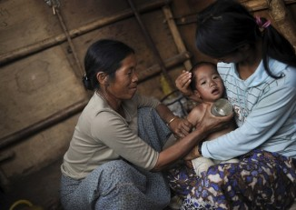 In this file photo, a Kachin woman applies traditional treatment to reduce her son's temperature at a refugee camp in Mansi Township, Kachin State, in January 2013. (Photo: Reuters)