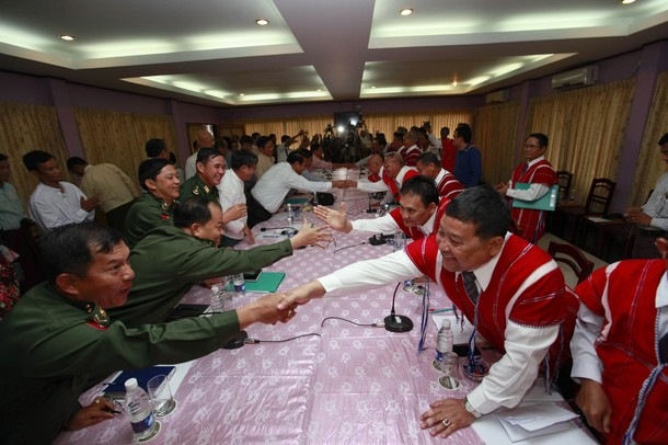 Representatives from Burma's government and the Karen National Union shake hands during 2012 peace talks in Hpa-an (PHOTO: Reuters)